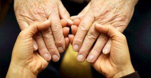 Caregiver and elder holding hands